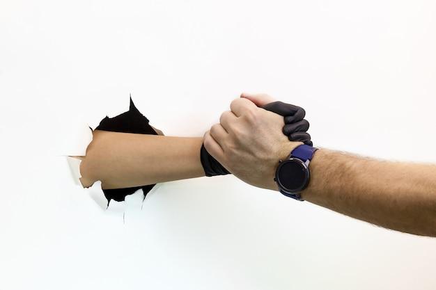 Vrouwelijke en mannelijke handen, één in een beschermende handschoen en de andere zonder handschoen, twee mensenhanddruk op een witte achtergrond