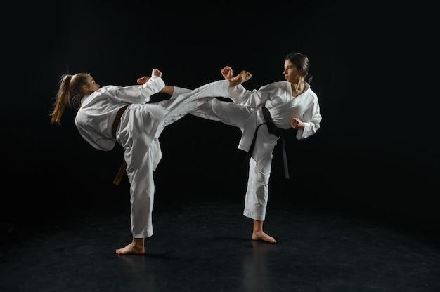 Vrouwelijke en mannelijke karatestrijders, strijd in actie, witte kimono. karateka over training, vechtsporten, vechtwedstrijden