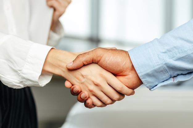 Vrouwelijke en mannelijke ondernemers handdruk close-up
