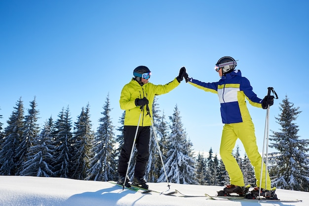 Vrouwelijke en mannelijke skiërs high five aan elkaar onder zonnige blauwe hemel. succesvol skiën tot aan de bergtop. volledige lengte.
