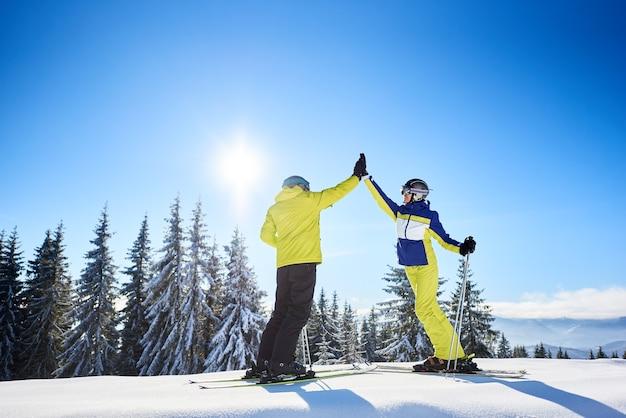 Vrouwelijke en mannelijke skiërs high five aan elkaar onder zonnige blauwe hemel