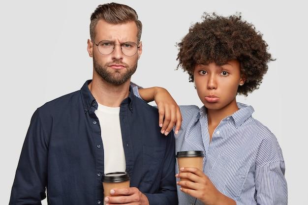 Vrouwelijke en mannelijke studenten van gemengd ras hebben ontevreden uitdrukkingen, drinken koffie na colleges, ontevreden over examenresultaten. afro-amerikaanse vrouw leunt naar de schouder van metgezel, staan samen