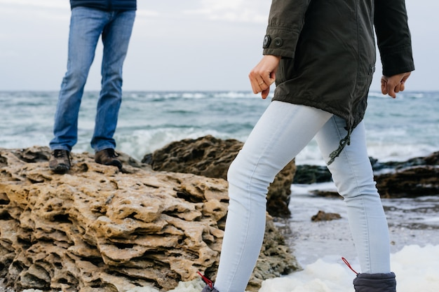 Vrouwelijke en mannelijke voeten in jeans op de rotsachtige kust in bewolkte dag