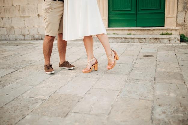 Vrouwelijke en mannelijke voeten op de stoep