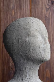 Vrouwelijke etalagepop hoofd cement op houten achtergrond