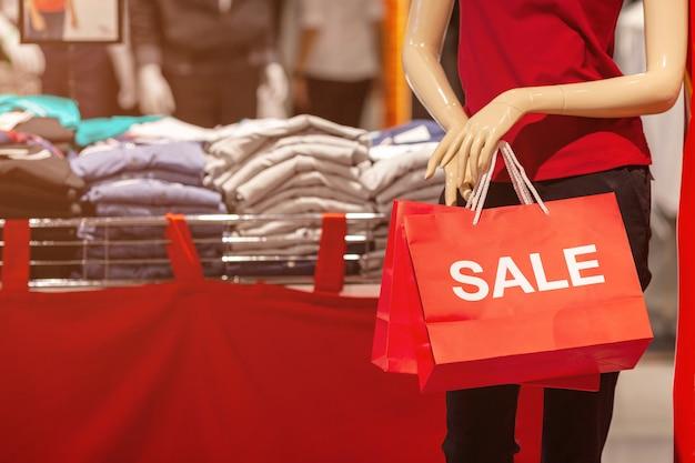 Vrouwelijke etalagepoppen met rode papieren boodschappentas met verkoop tekst in de winkel