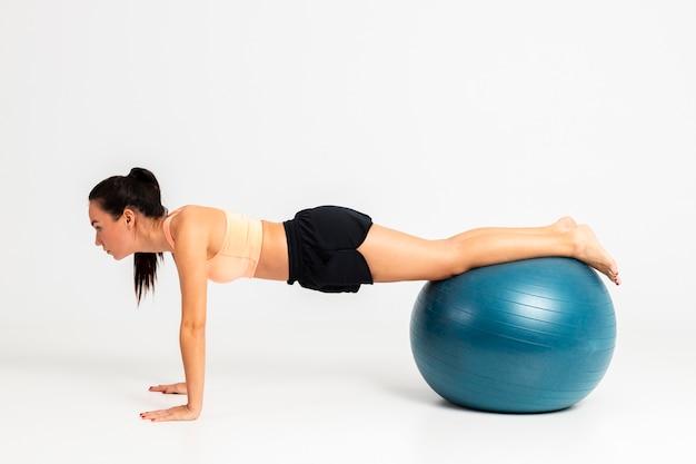 Vrouwelijke evenwichtsoefening op stuiterende bal
