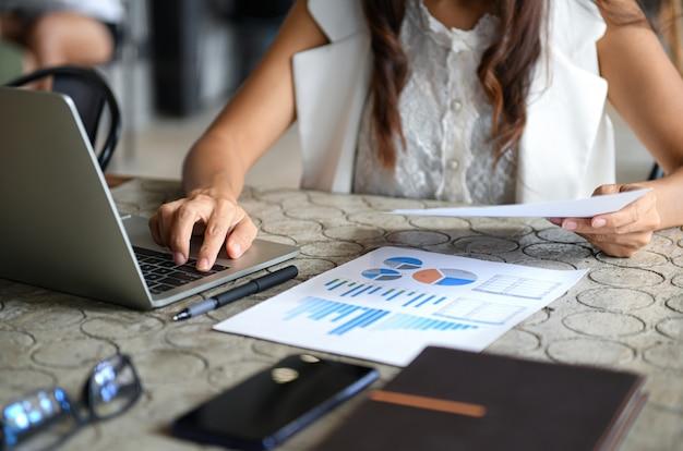 Vrouwelijke executive gebruikt laptop en controleert de gegevensgrafiek van het bedrijf.