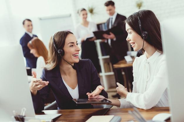 Vrouwelijke exploitanten van een callcenter communiceren met elkaar.