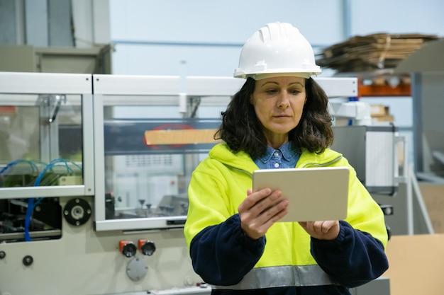 Vrouwelijke fabrieksarbeider die tabletcomputer ter plaatse met behulp van