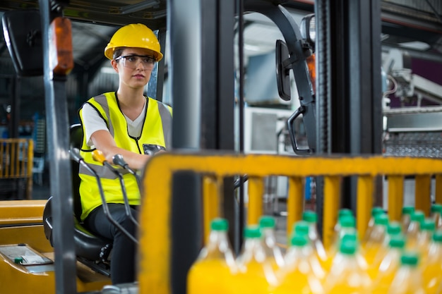 Vrouwelijke fabrieksarbeider drijvende vorkheftruck in fabriek