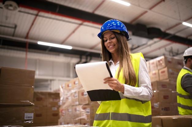Vrouwelijke fabrieksarbeider in reflecterend uniform met veiligheidshelm helm controleren nieuwe aankomst van goederen in magazijn