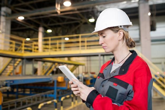 Vrouwelijke fabrieksarbeider met behulp van tablet pc