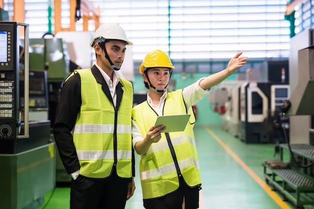 Vrouwelijke fabrieksarbeider rapporteert aan manager