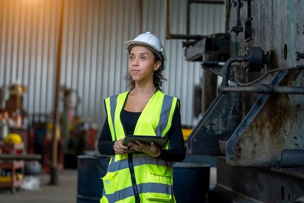 Vrouwelijke fabrieksarbeider werken en controleren met klembord in handen noodzakelijke notities op plant.