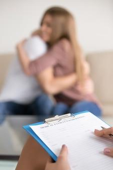 Vrouwelijke familiepsycholoog die informatie over paar in medische kaart vullen