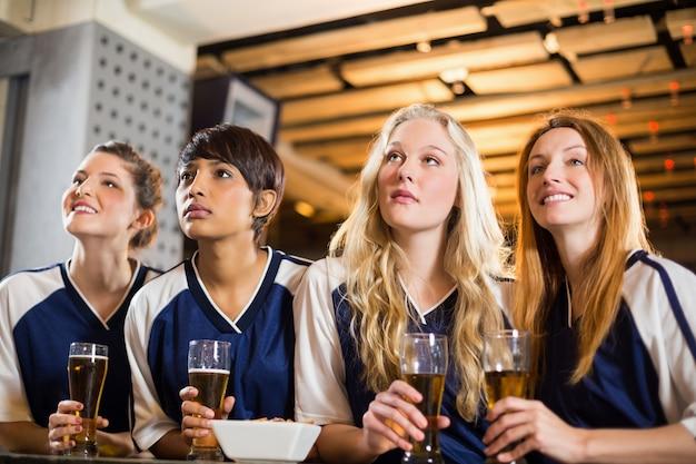 Vrouwelijke fan kijken naar voetbal op toog