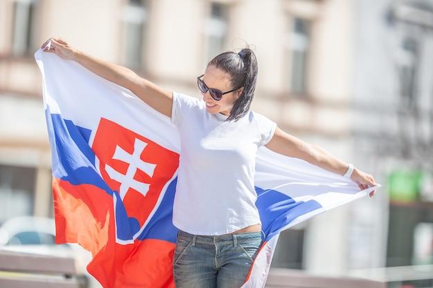 Vrouwelijke fan van slowakije lacht om wind die speelt met de vlag die ze achter haar rug houdt.