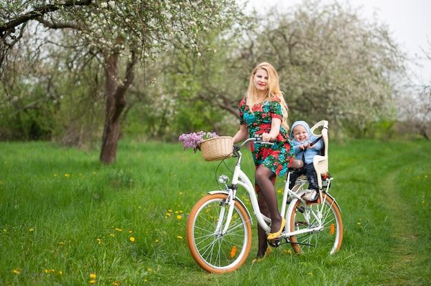 Vrouwelijke fiets van de blonde de vrouwelijke het berijden met baby als fietsvoorzitter