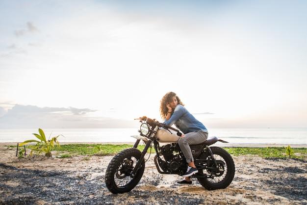 Vrouwelijke fietser die een motor van de koffieracer drijven