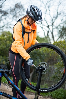 Vrouwelijke fietser die mountainbike herstelt