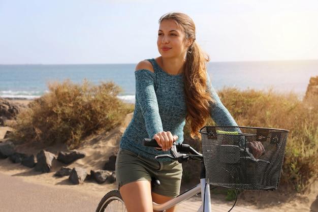 Vrouwelijke fietser rijdt langs de promenade op een zonnige dag