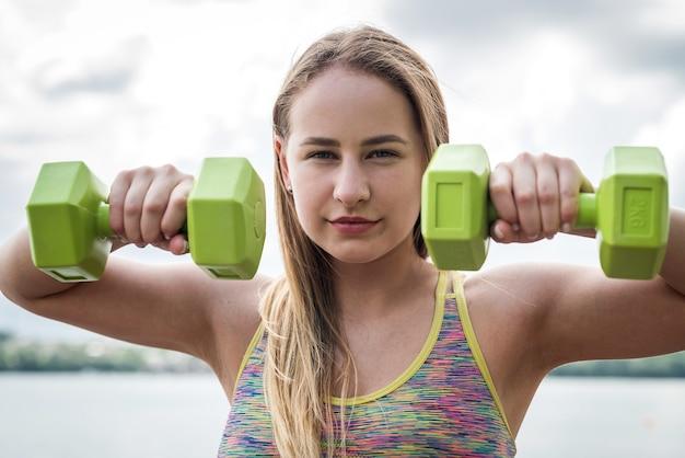 Vrouwelijke fitness instructeur doen trainen met halter in de buurt van meer