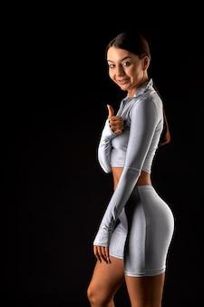 Vrouwelijke fitness model poseren met duimen omhoog