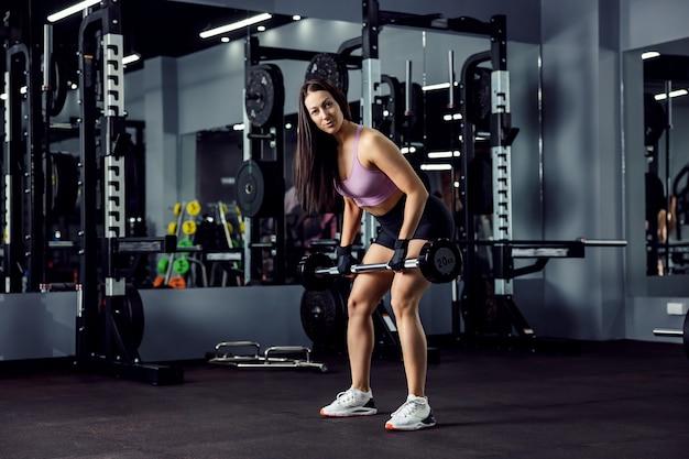Vrouwelijke fitnessbrunette doet arm- en bovenlichaamoefeningen en gebruikt een halter met handschoenen