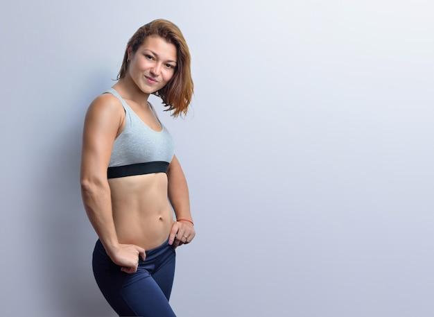 Vrouwelijke fitnesscoach met spieren in een grijze top en zwarte legging geïsoleerd op een witte achtergrond.