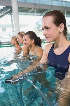 Vrouwelijke fitnessklasse die aqua-aerobics doet