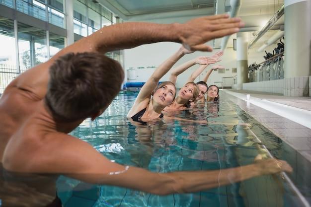 Vrouwelijke fitnessklasse die aquaaerobics met mannelijke instructeur doet