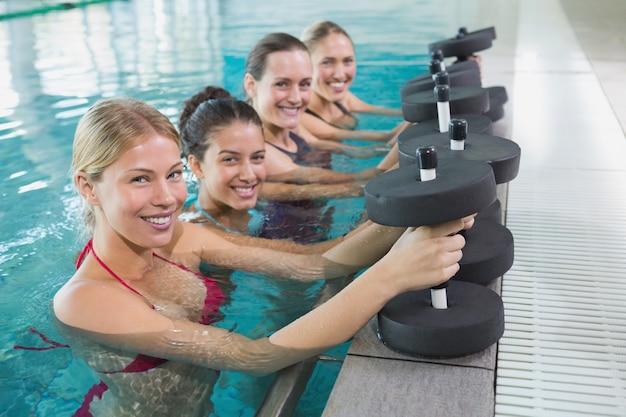 Vrouwelijke fitnessklasse die aquaaerobics met schuimdomoren doet