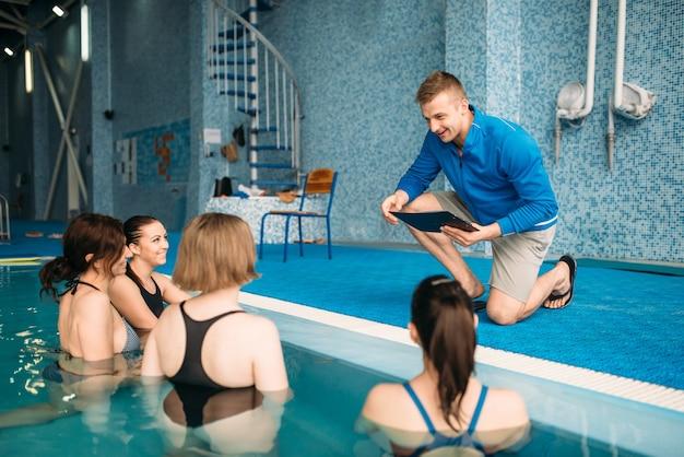 Vrouwelijke fitnessles met trainer, aqua-aerobics