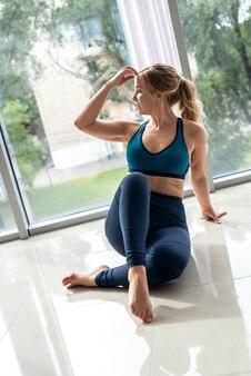 Vrouwelijke fitnesstrainer beoefent yoga voor een gezonde rug in de buurt van ramen in de sportschool