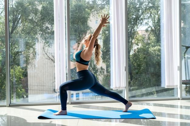 Vrouwelijke fitnesstrainer doet yoga therapie vormen van rugpijn