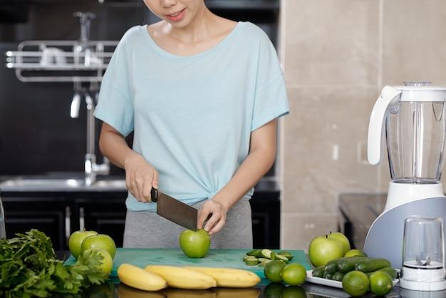 Vrouwelijke foodblogger snijdt appel met groentemes terwijl ze smoothie maakt in de keuken