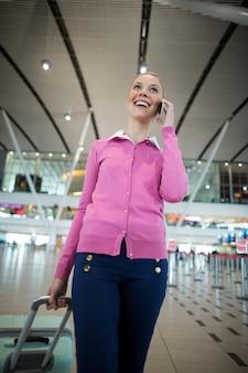 Vrouwelijke forens met bagage praten op mobiele telefoon