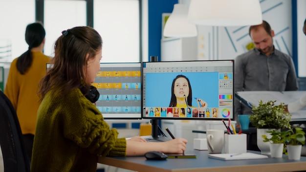 Vrouwelijke fotograaf bewerkt foto's in het kantoor van een creatief mediabureau en retoucheert de klant met styl...