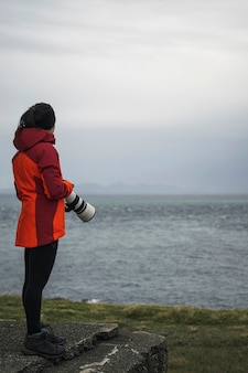 Vrouwelijke fotograaf bij vaternish lighthouse op isle of skye, schotland