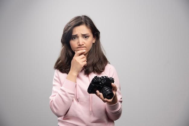 Vrouwelijke fotograaf camera houden en denken.