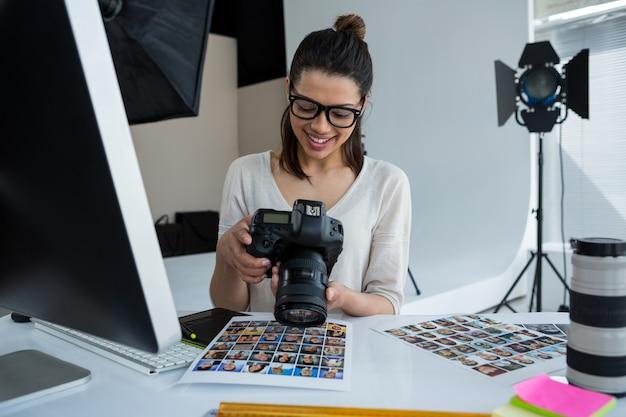 Vrouwelijke fotograaf die gemaakte foto's in haar digitale camera bekijkt