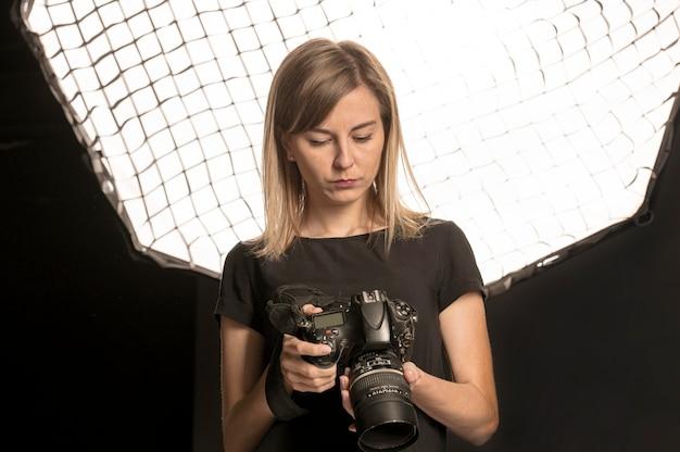 Vrouwelijke fotograaf die haar camera aanpast