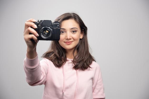 Vrouwelijke fotograaf die haar foto op grijze muur neemt.