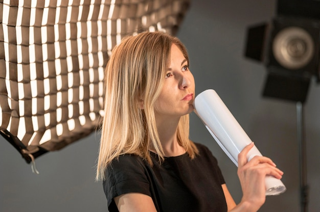 Vrouwelijke fotograaf die in studio denkt