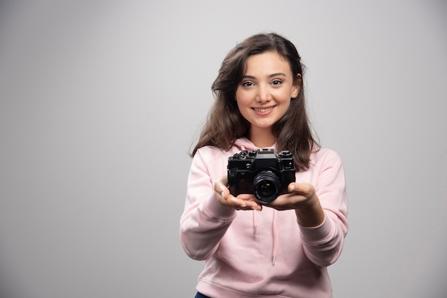 Vrouwelijke fotograaf die met camera op grijze muur glimlacht.