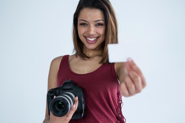 Vrouwelijke fotograaf die visitekaartje in studio toont