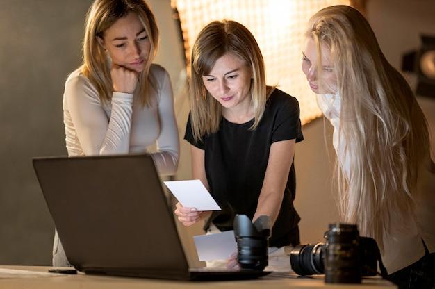 Vrouwelijke fotograaf en modellen kijken naar foto's