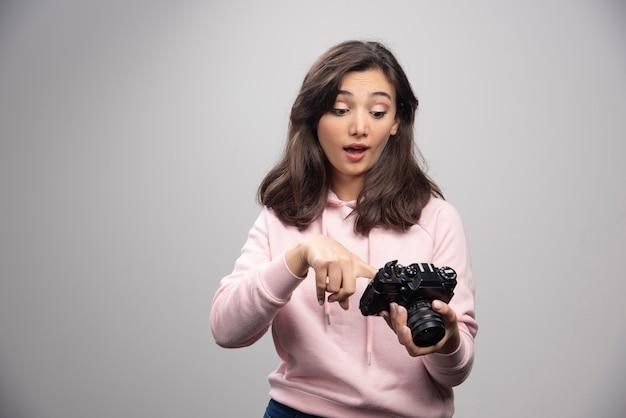 Vrouwelijke fotograaf gelukkig kijken naar foto's op de camera.