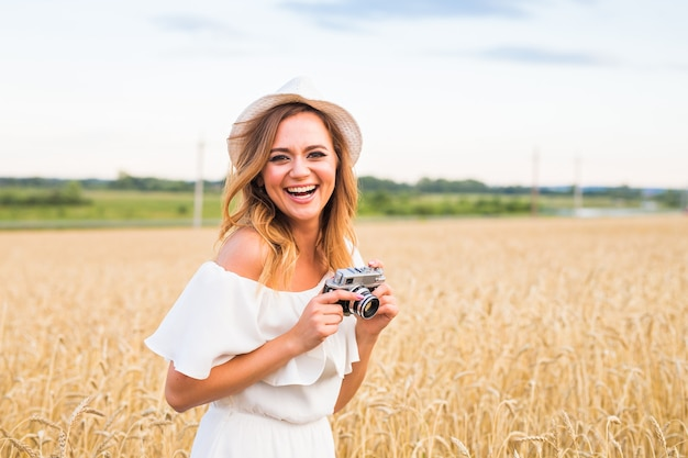 Vrouwelijke fotograaf in het veld met een camera die foto's maakt.